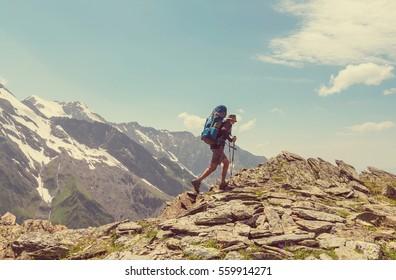 Hiker going along green hills in Caucasus mountains, Svaneti,Georgia. Summer season.