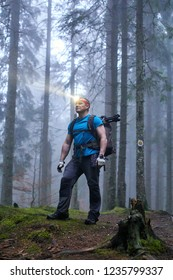 Hiker with headlamp and backpack on a trail in the forest at night