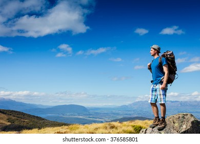 Hiker hiking with backpack looking at mountain view. New Zealand