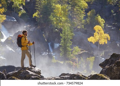 Hiker hiking with backpack looking at waterfall in park in beautiful autumn nature landscape. Portrait of male adult back standing outdoor.