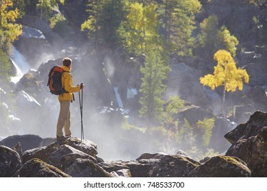 Hiker hiking with backpack looking at waterfall in park in beautiful summer nature landscape. Portrait of male adult back standing outdoor.