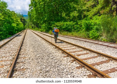 A hiker with his backpack is walking along an old railway near old railway station at national park of Oiti in Central Greece
