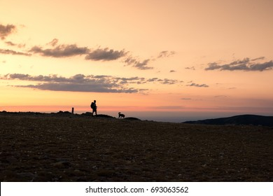 Hiker and his dog walk down the mountain in an amazing sunset. Navacerrada, Spain.