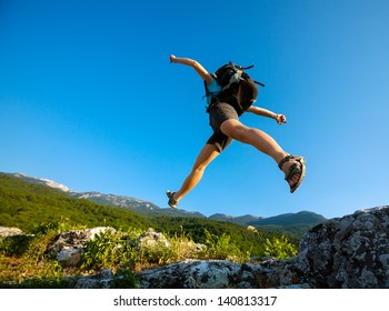 Hiker jumps over the rock