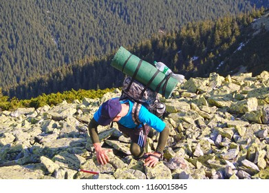 Hiker keep get out from rocky ascent.  Dangeous situation in Carpathian mountains.
