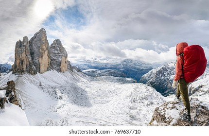 hiker with knapsack look on panorama view of Dolomites mountain in Italy at sunset. Tre Cime di Lavaredo mountain.