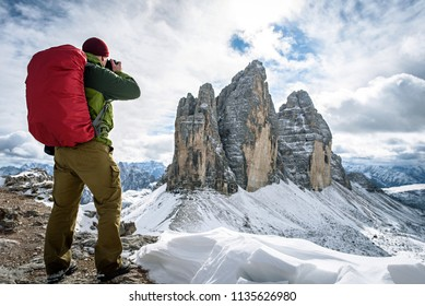 hiker with knapsack take a photograph panorama view of Dolomites mountain in Italy at sunset. Tre Cime di Lavaredo mountain.