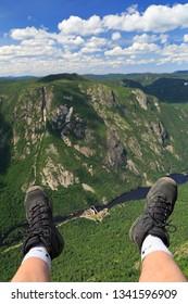 Hiker legs and boots at Acropoles de Draveurs above the canyon, Hautes-Gorges-de-la-Rivière-Malbaie National Park, Quebec in Canada