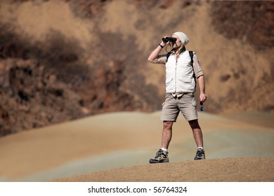 Hiker looking away through binoculars