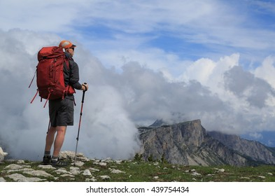 Hiker looking at the clouds over the mountains during an outdoor adventure.