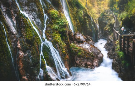 Hiker looking at gorgeous waterfalls in a magical forest.