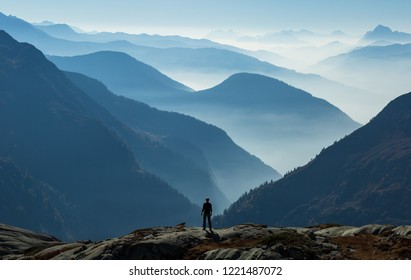 Hiker looking at the many layers of foggy, blue mountains. Near Chamonix, France.