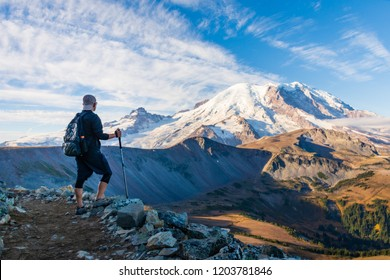 A Hiker looking at Mount Rainier on a Sunny Morning/Day