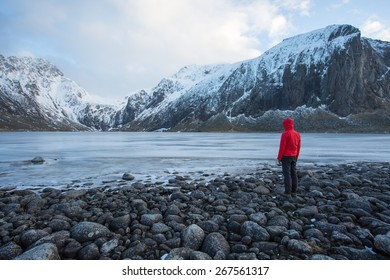Hiker looking out over iced-over lake near Eggum Beach, Lofoten, Norway