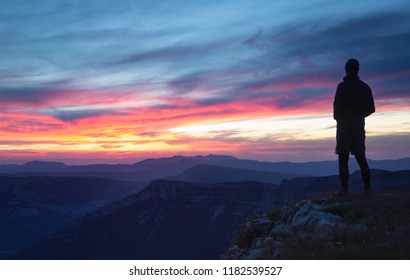Hiker looking at a pink sunset in a mountainous wilderness.