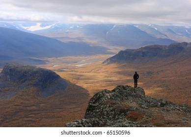Hiker looking at Rapadalen valley in autumn colors. Sarek, Sweden