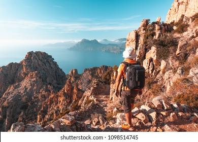 Randonneur admirant la vue sur les Calanques de Piana en Corse, France