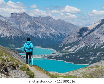 Hiker looks lakes of Cancano in Valtellina. Mountain landscapes.