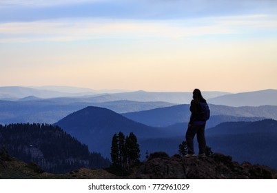 A hiker looks out over the valley admiring the expanse of mountains before her
