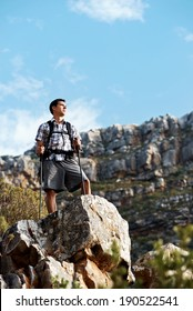 A hiker male standing on a mountain cliff in a mountain range with copyspace