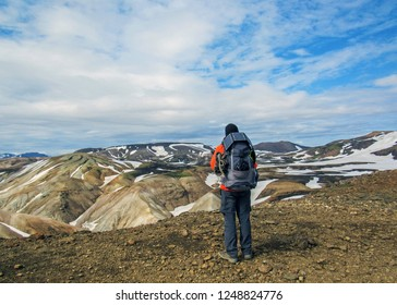 Hiker man alone into the wild admiring volcanic landscape with rhyolite mountains and snow with heavy backpack. Travel lifestyle adventure wanderlust concept, summer vacations outdoor