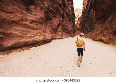 Hiker man with back pack  walking and explore  canyon in Jordan . Travel and adventure concept.