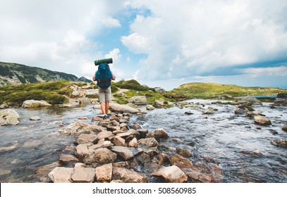 Hiker man with backpack crossing a river on stones in bulgarian mountains. Hiking and leisure theme. Image with sunlight effect