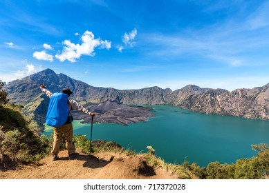 Hiker man with backpack spreading hand enjoy and happy with active volcano Baru Jari, Lake Segara Anak and summit of Rinjani mountain view after finished climbing at Rinjani mountain,