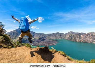 Hiker man with backpack spreading hand, jumping and happy with active volcano Baru Jari, Lake Segara Anak and summit of Rinjani mountain after finished climbing at Rinjani mountain, Lombok Indonesia.