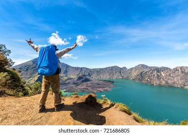 Hiker man with backpack spreading hand and enjoy with active volcano Baru Jari, Lake Segara Anak and summit of Rinjani mountain view after finished climbing at Rinjani mountain, Lombok, Indonesia