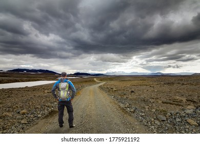 Hiker Man with Backpack standing on hiking trail dirt road in arctic desert. Kaldidalur, Road F550, Iceland.