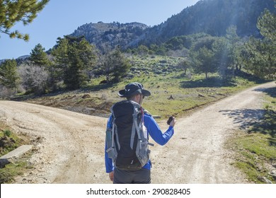 Hiker man choose in a road fork between two different path directions at the forest in mountain