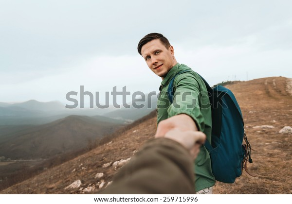 Hiker man holding woman's hand and leading her on nature outdoor. Focus on man. Point of view shot