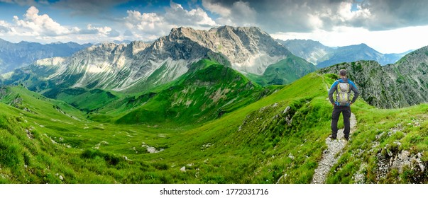 Hiker Man on Hiking Trail with Backpack standing relaxed and enjoying panoramic view to mountains. Alps, Hohe Gaenge, Allgau, Bad Hindelang, Hinterstein, Bavaria, Germany.