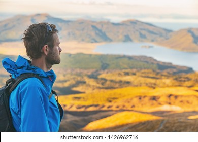 Hiker man on New Zealand trek hike tramping on outdoor trail mountain landscape. Young caucasian tramper walking with backpack at sunset nature.