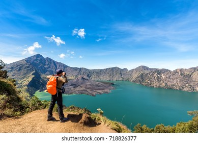 Hiker man with orange backpack standing, enjoy and happy with active volcano Baru Jari, Lake Segara Anak and summit of Mount Rinjani view after finished climbing at Rinjani mountain, Lombok, Indonesia