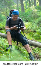 Hiker man is resting and determines his position in the forest with the help of GPS receiver and map, sitting on a background of green wood.