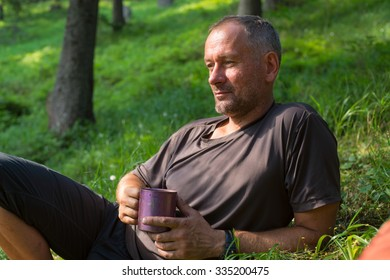 Hiker man is resting, lying on the green grass with cup of coffee, thinking about something. The mood for reflection.  Blurred green background.