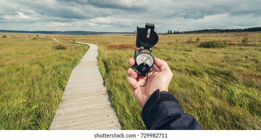 Hiker man searching direction with a compass in a bog landscape with wooden trail. View of hands. Point of view shot.
