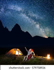 Hiker man showing his lady stars and Milky way in the night sky. Couple covered with a plaid sitting near the lighting tent and campfire. On the background silhouette of the mountains. Long exposure