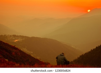 a hiker man sits in a tired pose on a mountainside above a beautiful valley at sunset against a red sky