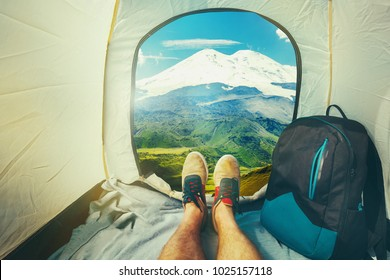 Hiker Man Sitting In A Tourist Tent by The Elbrus Mount Travel Discovery Concept. View Of Legs. Point Of View Shot