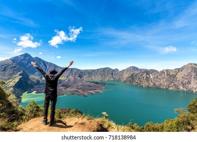 Hiker man spreading hand, enjoy and happy with active volcano Baru Jari, Lake Segara Anak and summit of Rinjani mountain view after finished climbing at Rinjani mountain, Lombok, Indonesia.