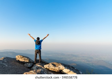Hiker man spreading hand on top of mountain and enjoy valley view.