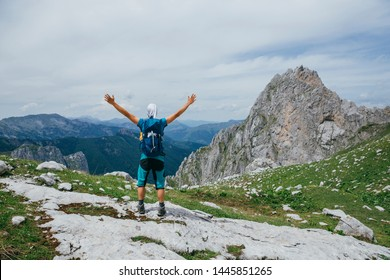 Hiker man standing with hands up achieving the top. Conceptual design. Successful man hiker open arms on mountain top. Man in sportswear in the mountains. Montenegro, Prokletije National Park