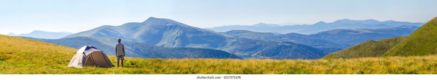 Hiker man standing near camping tent in carpathian mountains. Tourist enjoy mountain view. Travel concept.