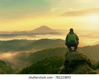 Hiker man take a rest on mountain peak. Man sit on sharp summit and enjoy spectacular view.  Colorful autumn landscape. Bright morning Sun shining in sky.