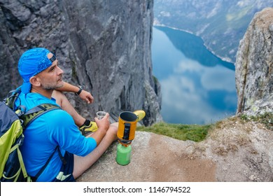 Hiker man traveler in blue sportswear preparing hot drink with a portable gas burner on the high in Norway mountains. Top view. Adventure, travel, tourism, hike and people concept