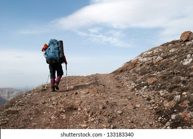 hiker in a mountain with blue sky on the background