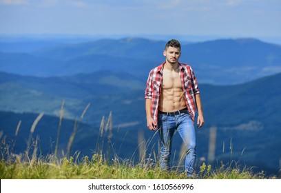 Hiker muscular torso reach mountain peak. Hiking concept. Man stand top mountain landscape background. Athlete guy relax mountains. Beautiful environment. Muscular tourist walk mountain hill.